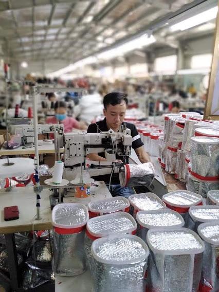 Một công nhân đang may túi giữ nhiệt trên chuyền may